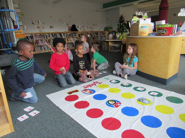 Five students with arrow cards in front of twister map placing cards for a path to follow.